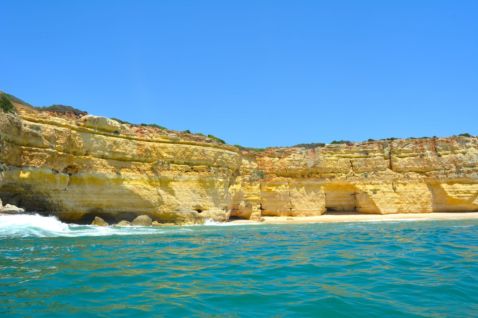 In this photo, you will see golden cliffs and turquoise waters. It was taken in the region of Algarve in Portugal known for its gorgeous coastline.