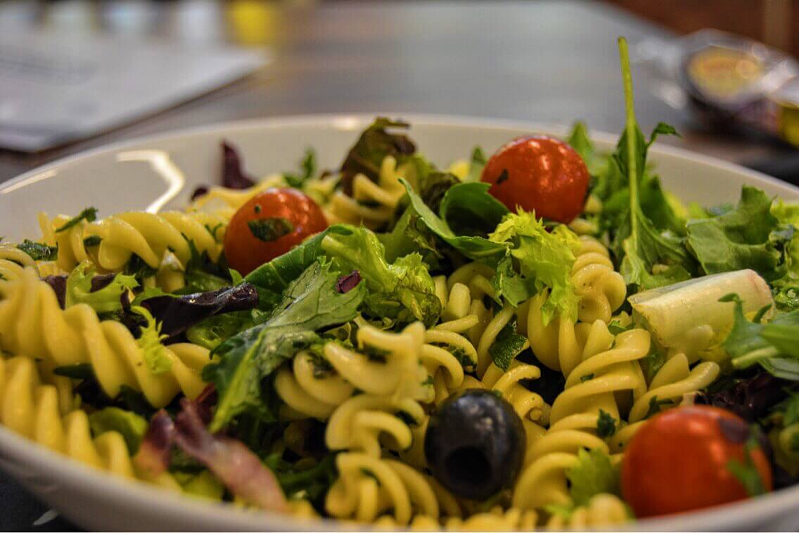 A bowl of pasta salad with tomatoes, pasta and greens
