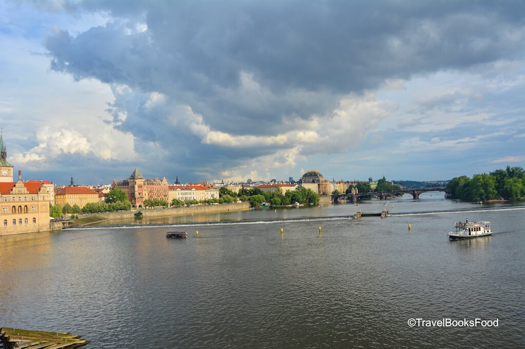 A photo of Prague from the iconic Charles Bridge with a fiery sky and the river in it