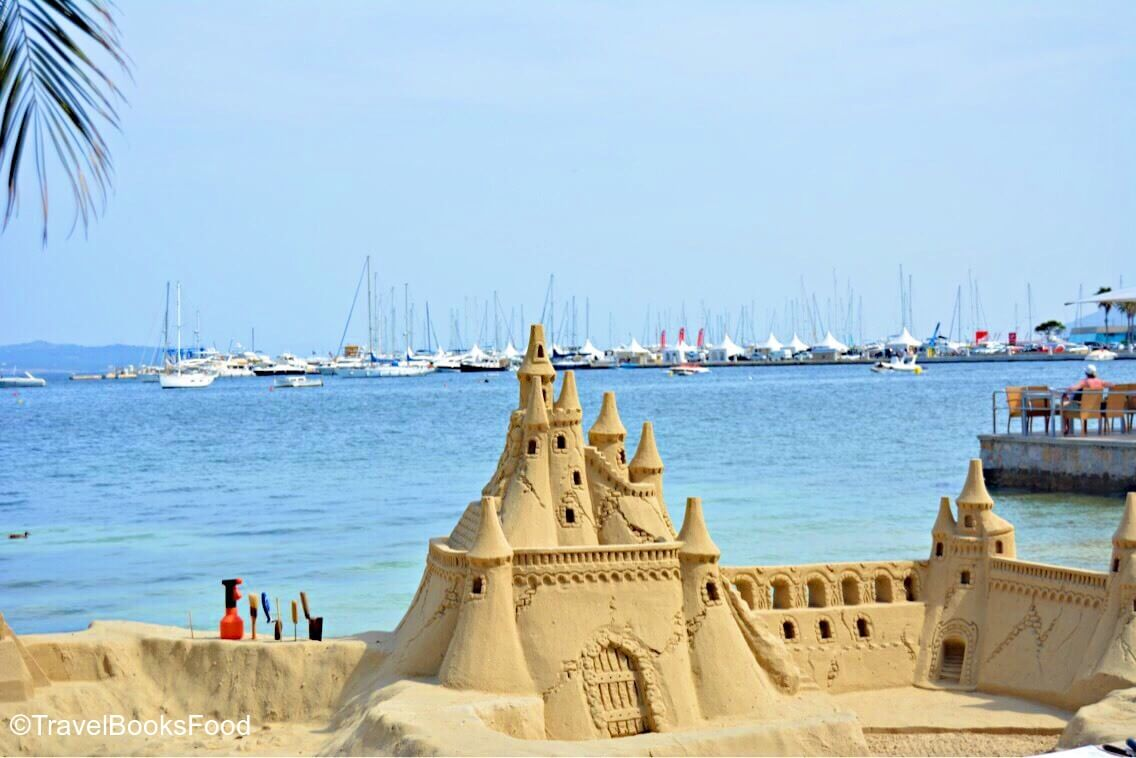 A sand castle in Mallorca, Spain with boats in the distance