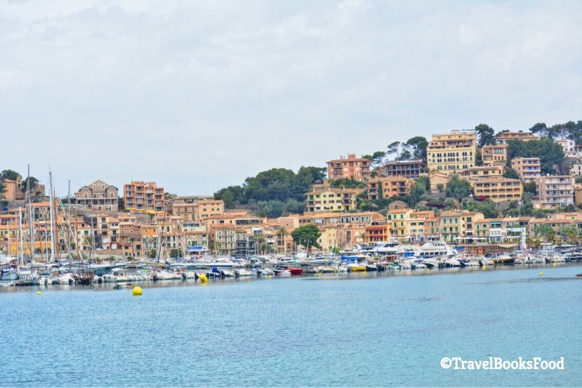 This is a photo of Port De Soller Harbour with the boats and cream houses in the distance
