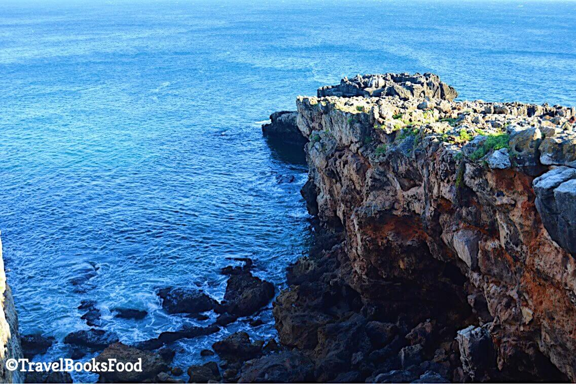 This is a photo of some rocks and the sea at the Cascais beach in Portugal