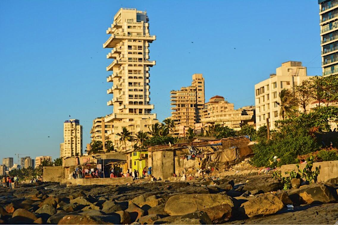 This is the view of the rocks and slums alongside the big residential buildings near Bandra in Mumbai