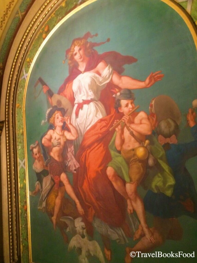A painting of a lady surrounded by kids inside the Vienna Opera House