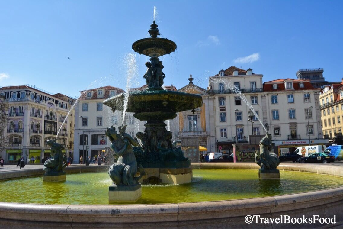 A photo of a fountain in Rossio Square in Lisbon surrounded by buildings.