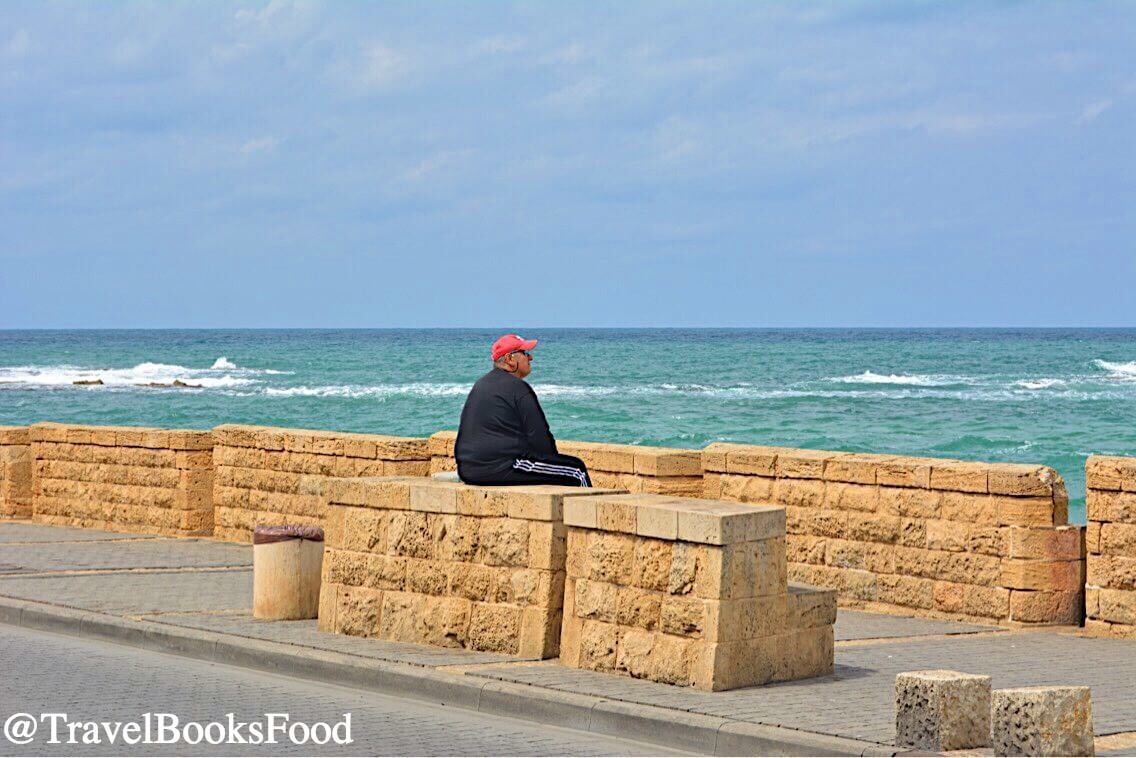 A lone man staring into the Ocean along the Tel Aviv Promenade