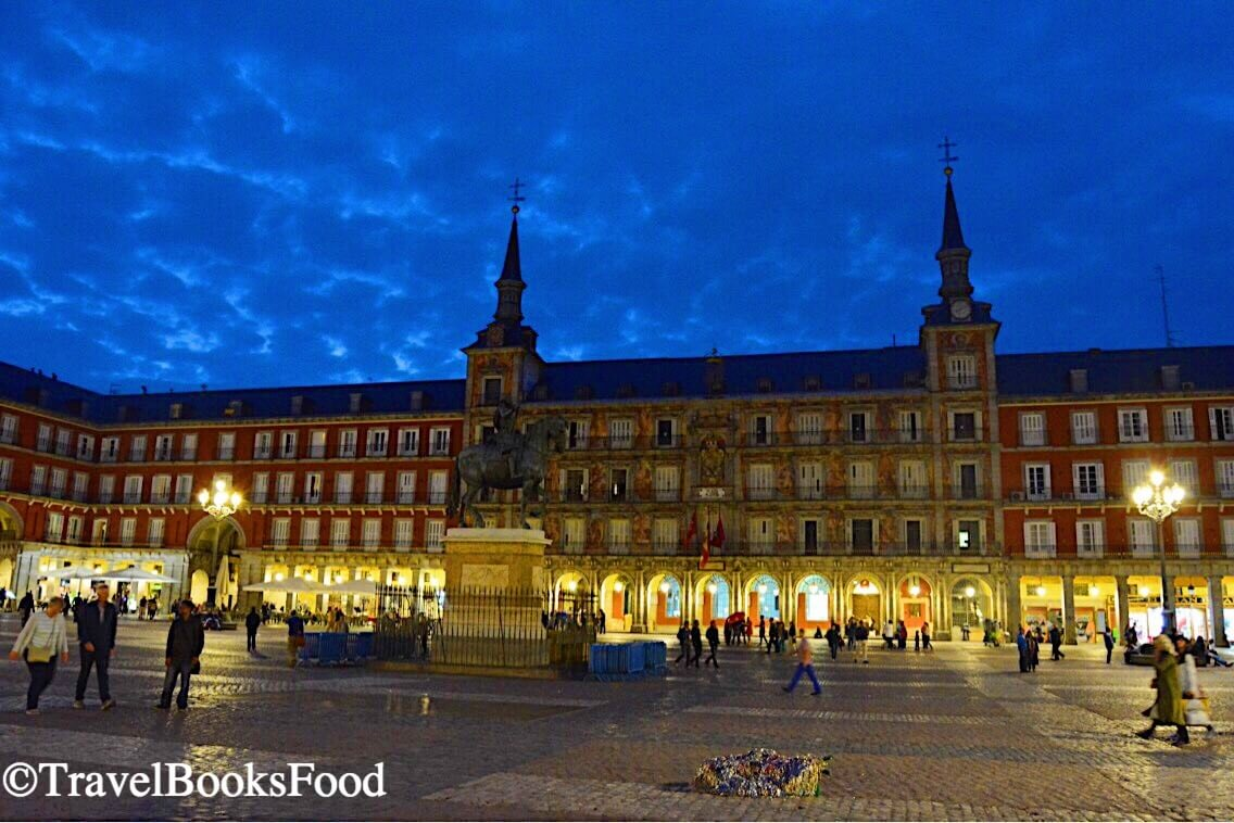 Plaza Mayor is a huge plaza in Madrid, Spain. It is a red building covering four sides of a plaza and this is a photo of it during blue hour