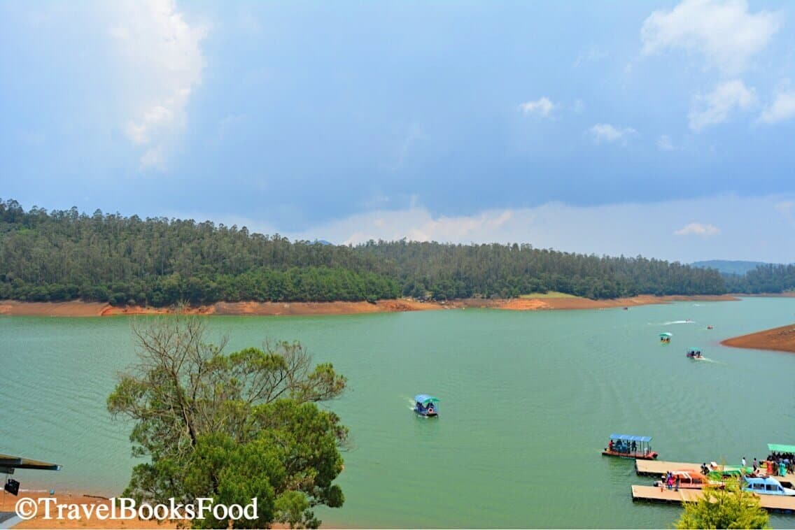 A photo of the Pykara Lake in Ooty. It is a green lake and people go for boating here amidst the numerous trees