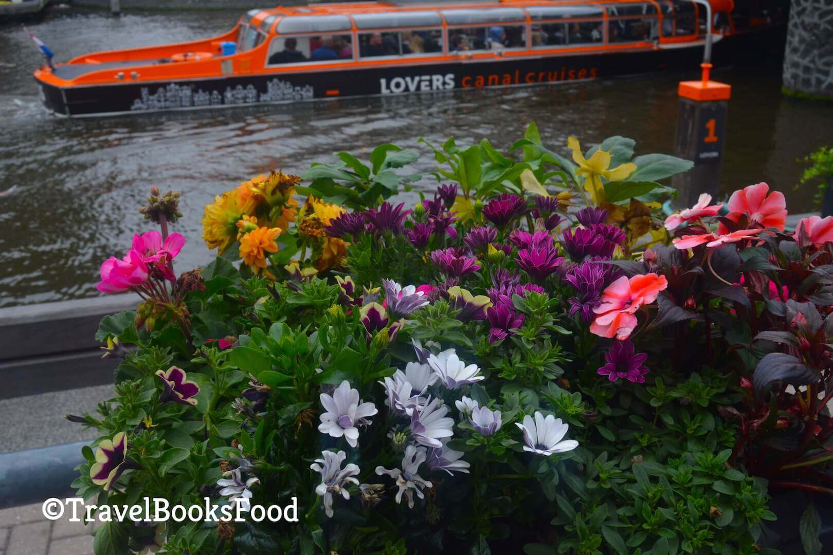 Flower basket overlooking a canal cruise boat in Amsterdam Canals