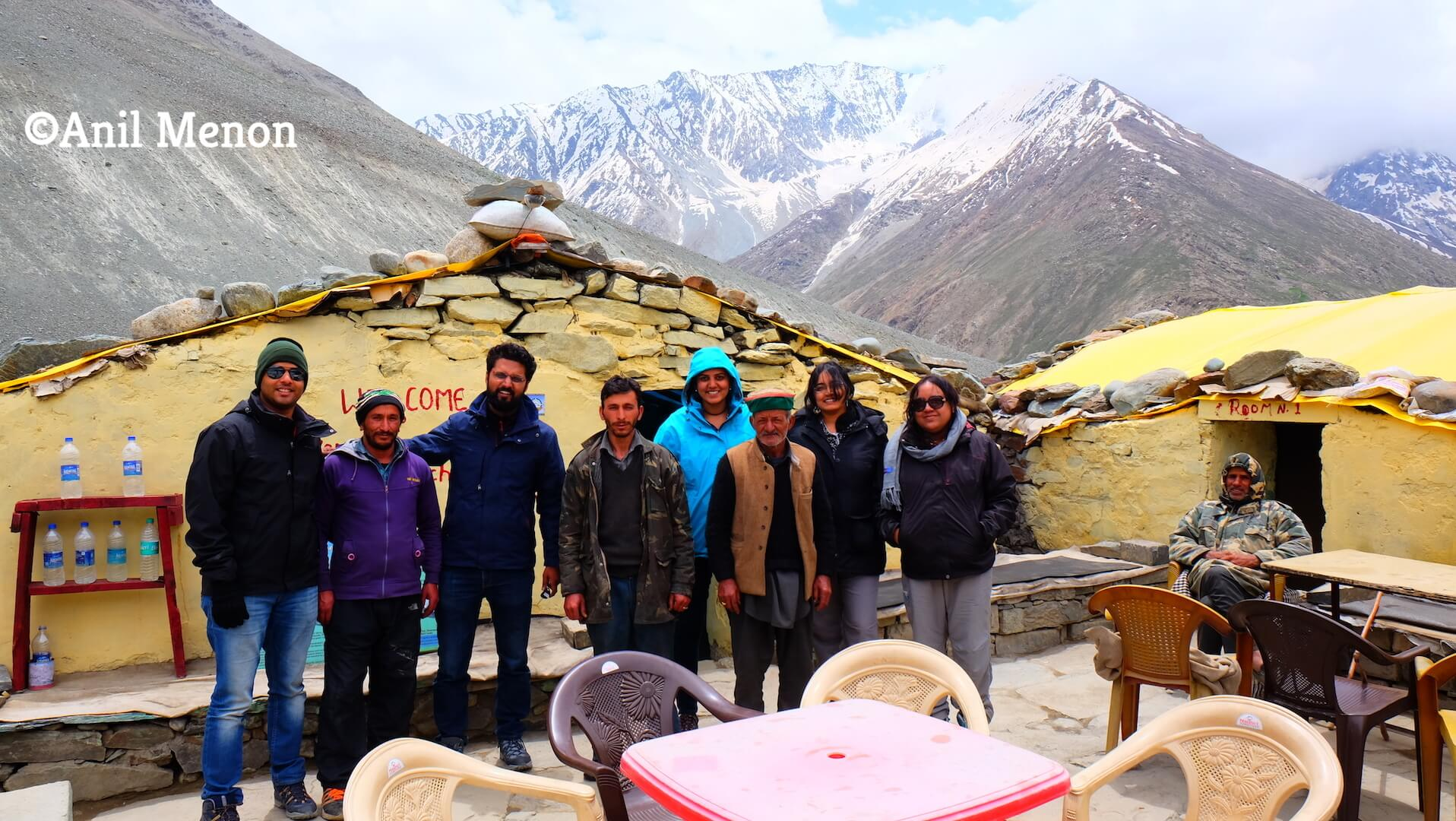 A photo of us with the owner of the rest stop and his helpers outside our huts in Himalayas