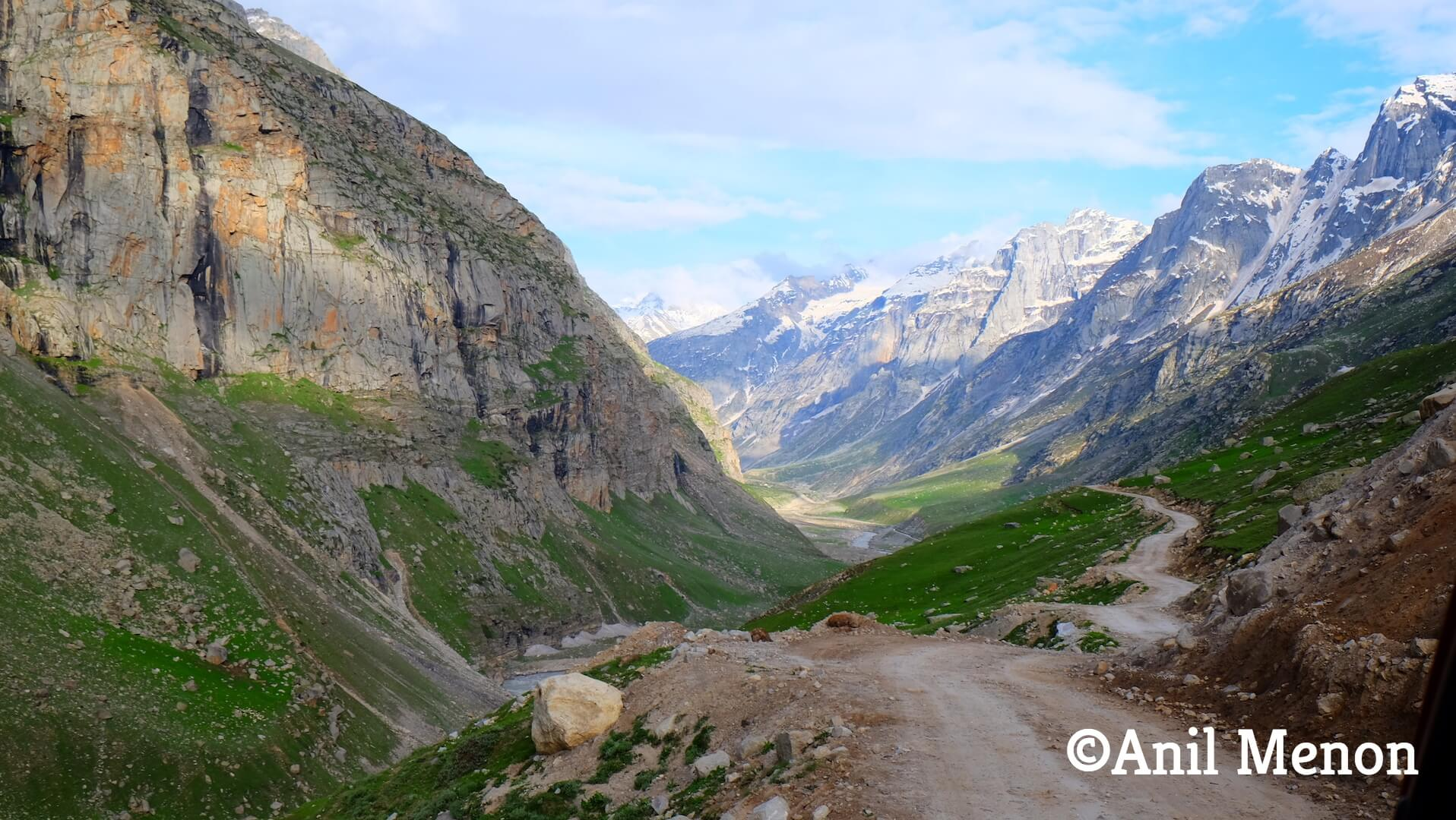 A photo of some dirt roads in the Himalayas surrounded by a majestic mountainous range