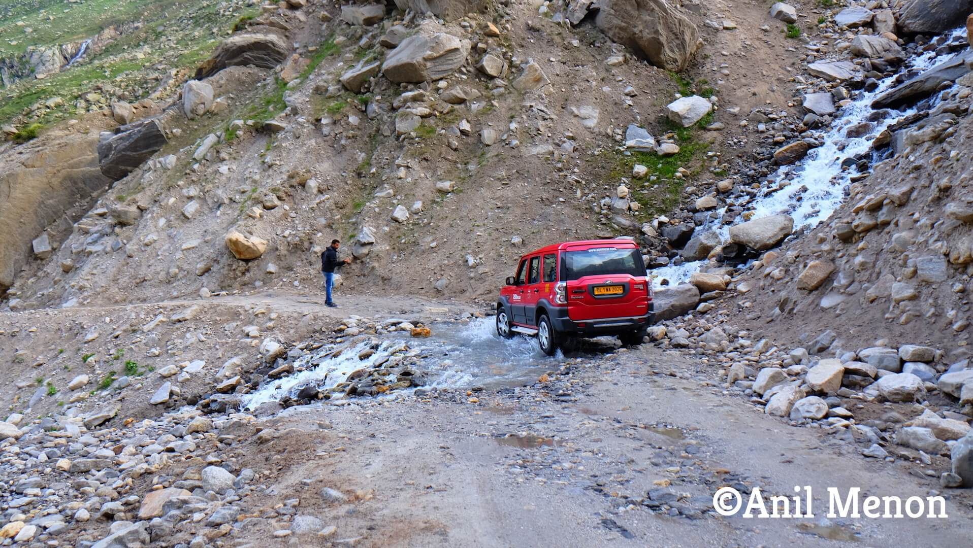 A red car navigating through a stream and bad roads
