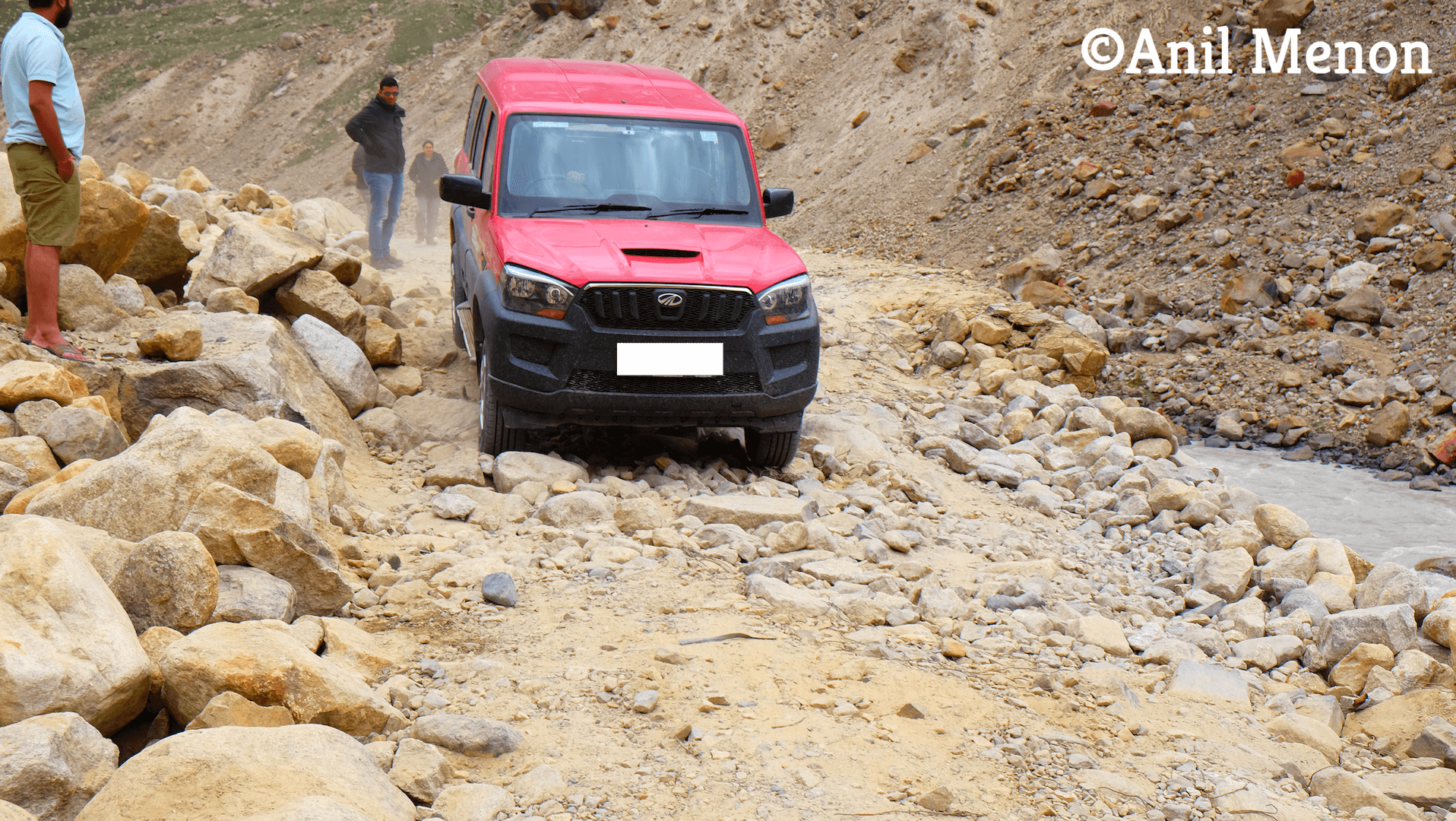 A red Scorpio trying to navigate through some really bad roads with people looking on.