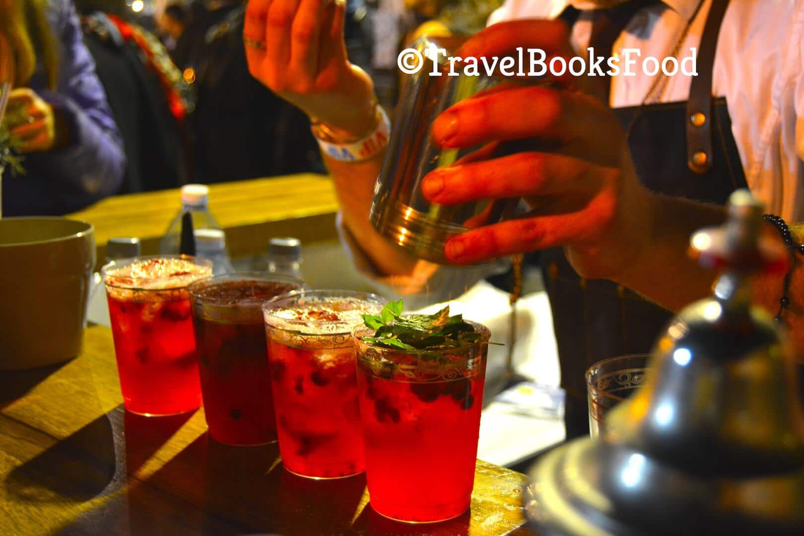 A waiter mixing four glasses of Pomegranate based cocktails