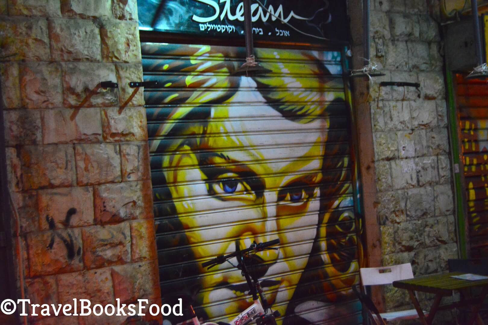 A photo of a painting of a lady on a shop shutter in Mahane Yehuda in Jerusalem.
