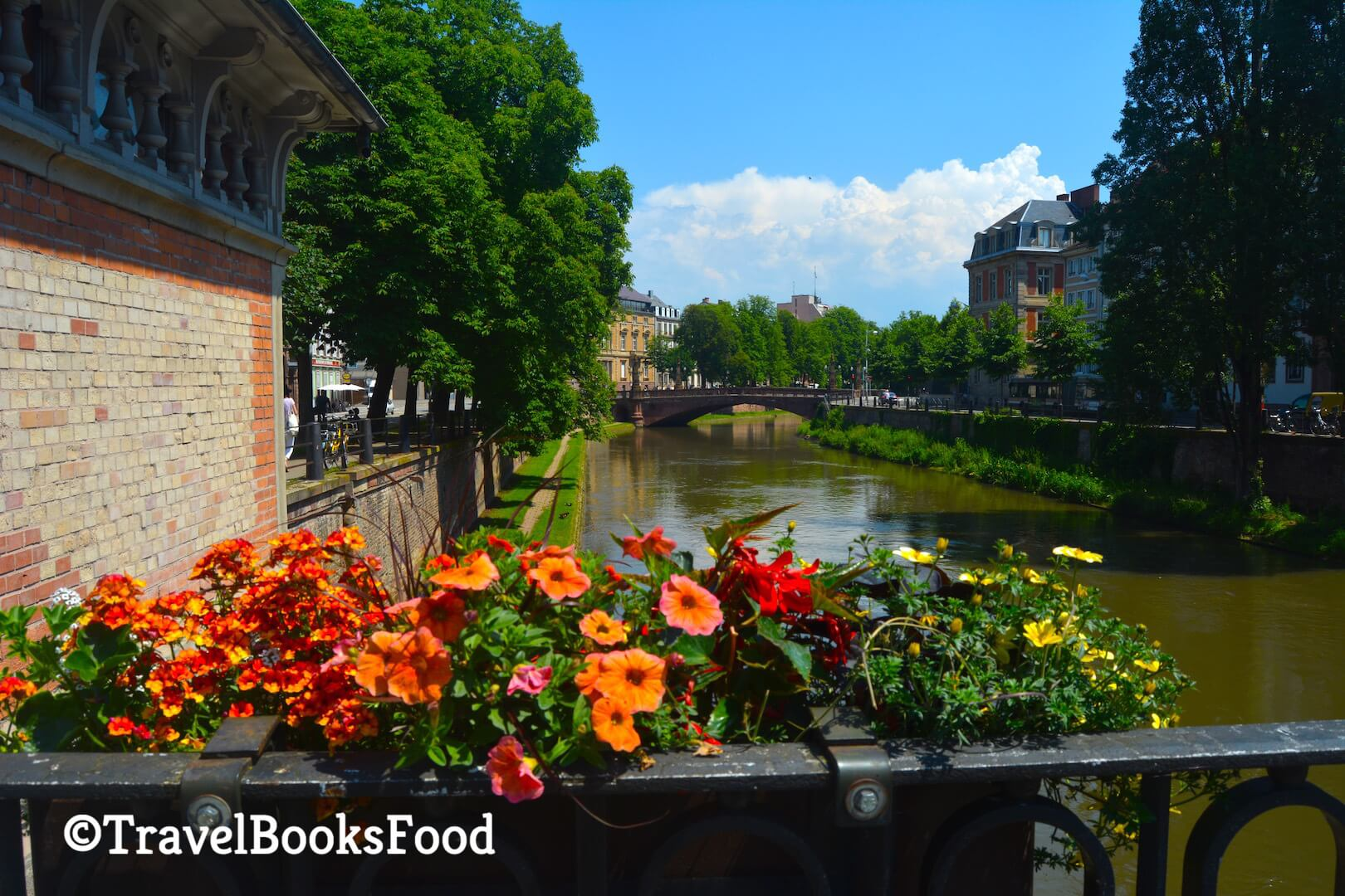 A view of the bridges of Strasbourg in France with some flower baskets on one of the bridges