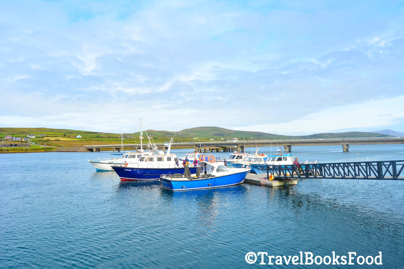 A photo of Portmagee Harbour with crystal clear blue water and few boats with a bridge and some mountains in the distance