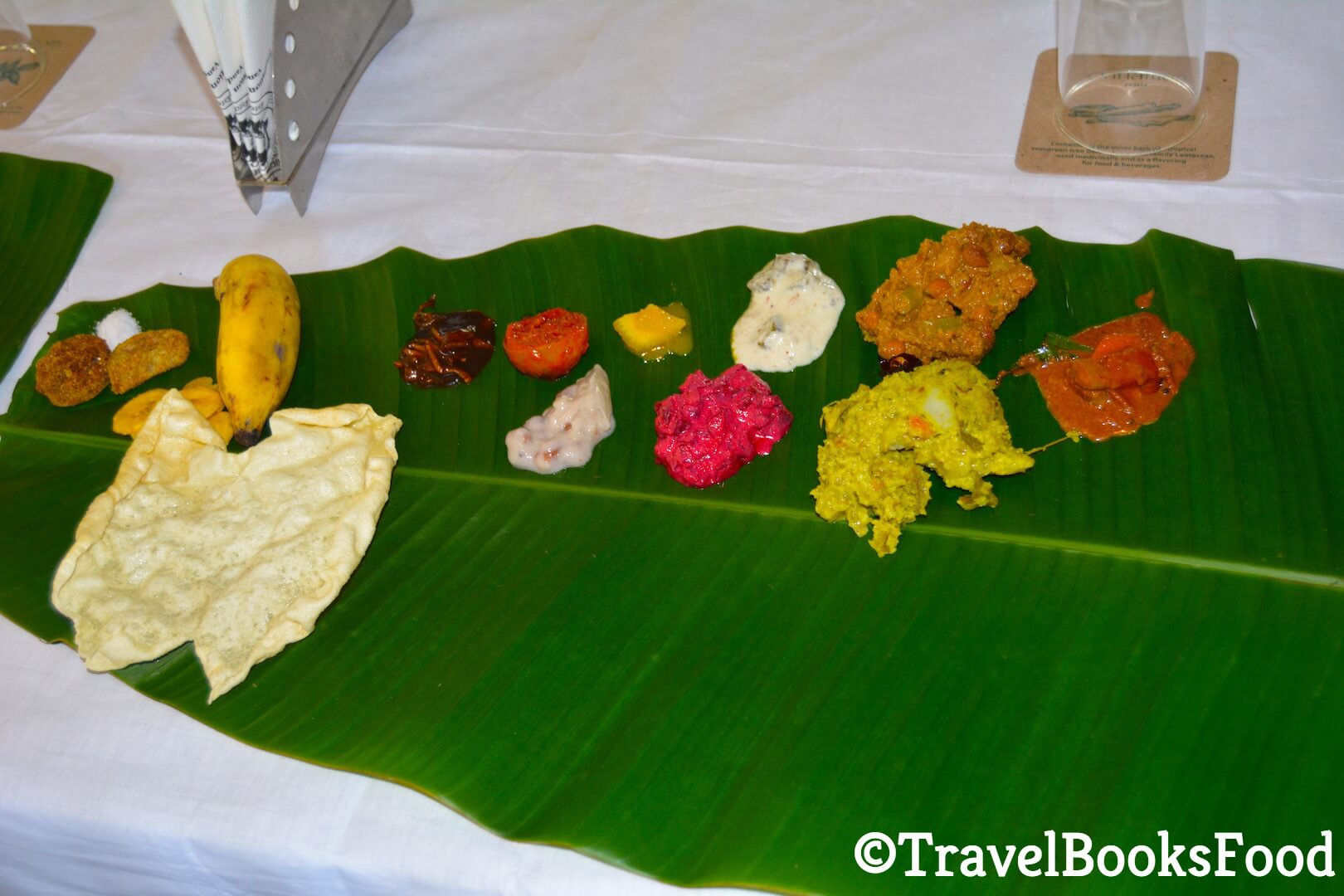 Photo of a traditional Kerala Vegetarian Meal (Sadhya) served in a green plantain leaf. There are at least 12-14 types of foods in this photo.