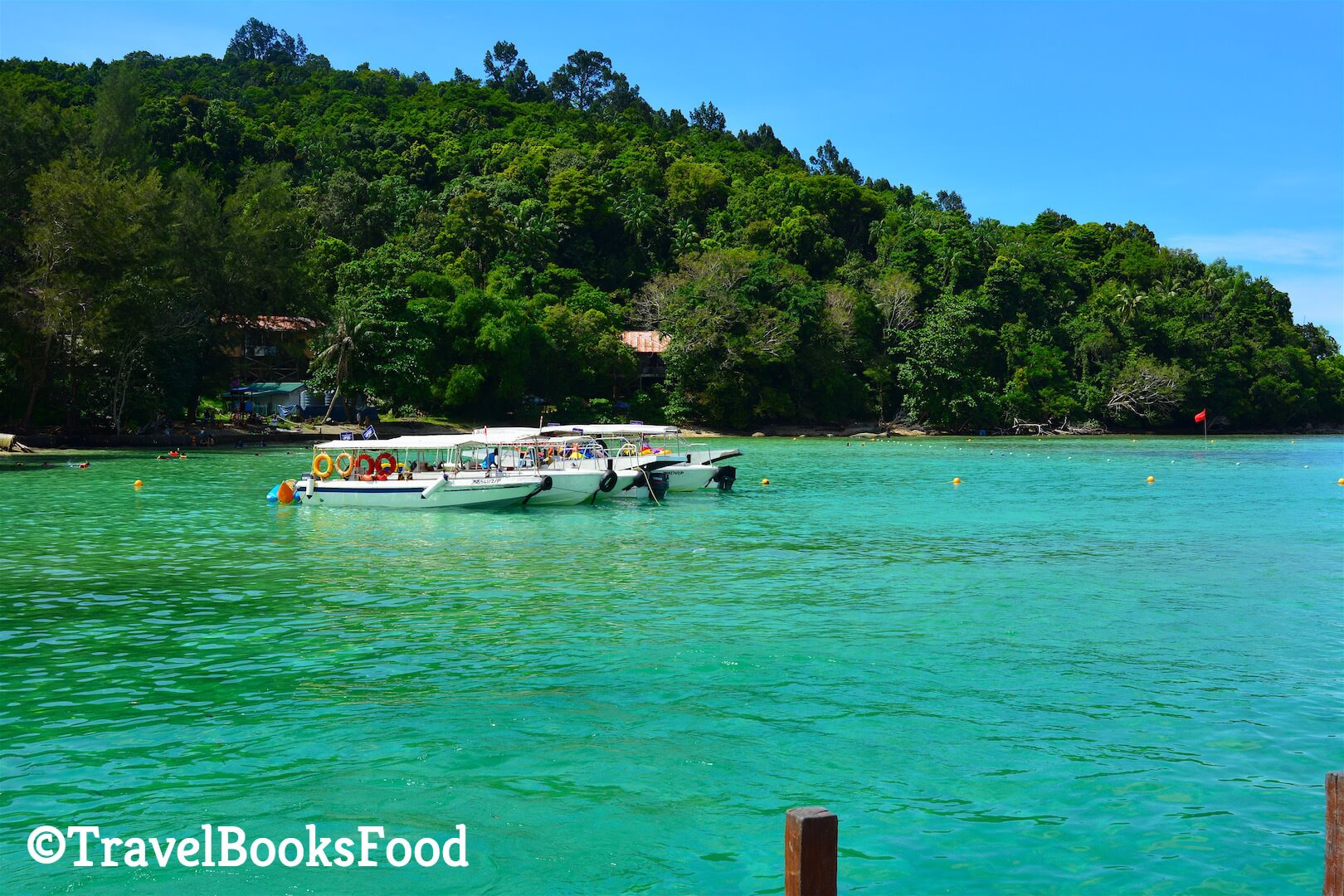 Picture of three white boats surrounded by turquoise blue waters in Sapi Island, Kota Kinabalu, Malaysia