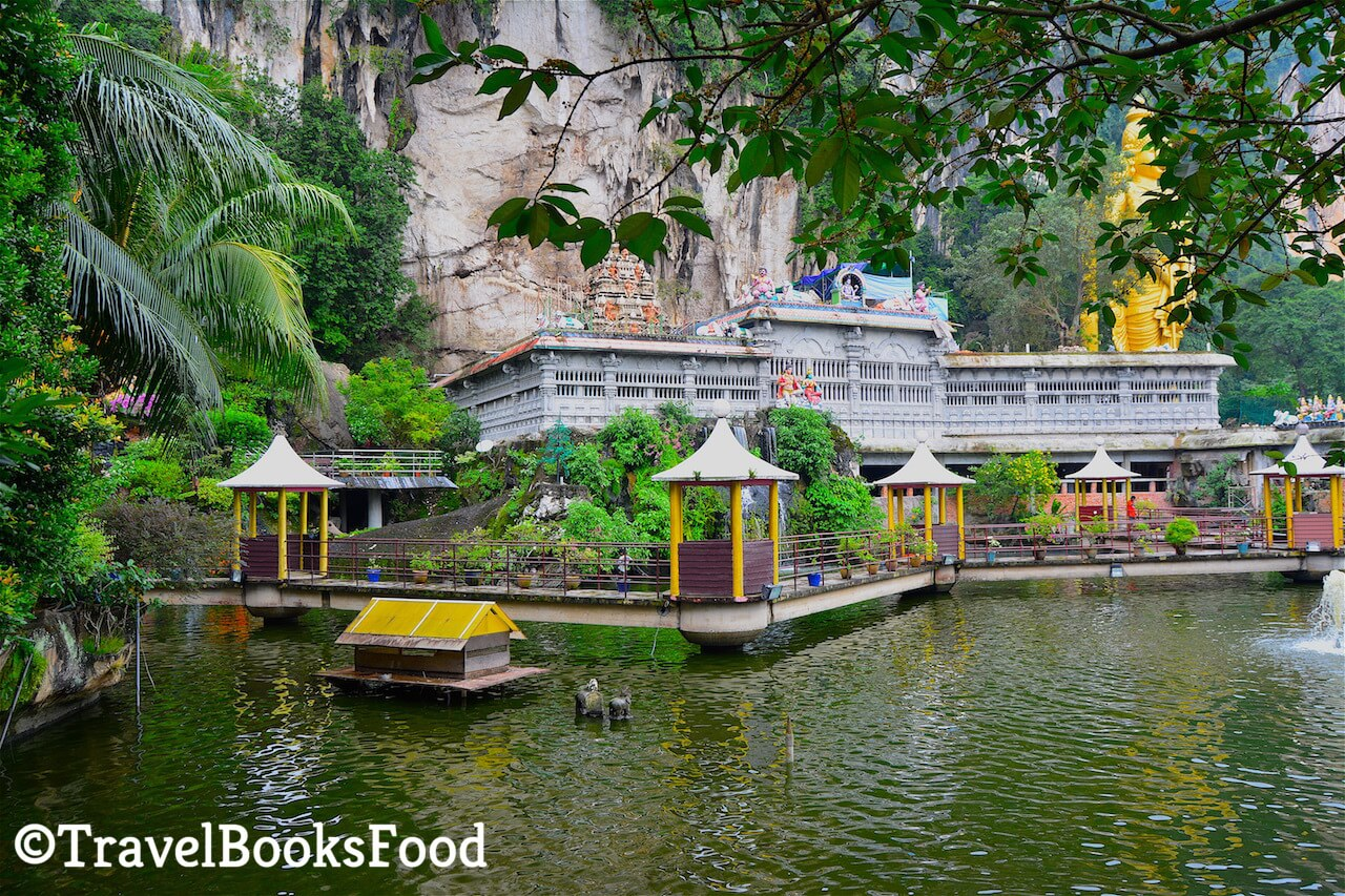 A photo of the entrance of the Batu Caves from another angle. You can see the statue in the distance with a lake in the front of it
