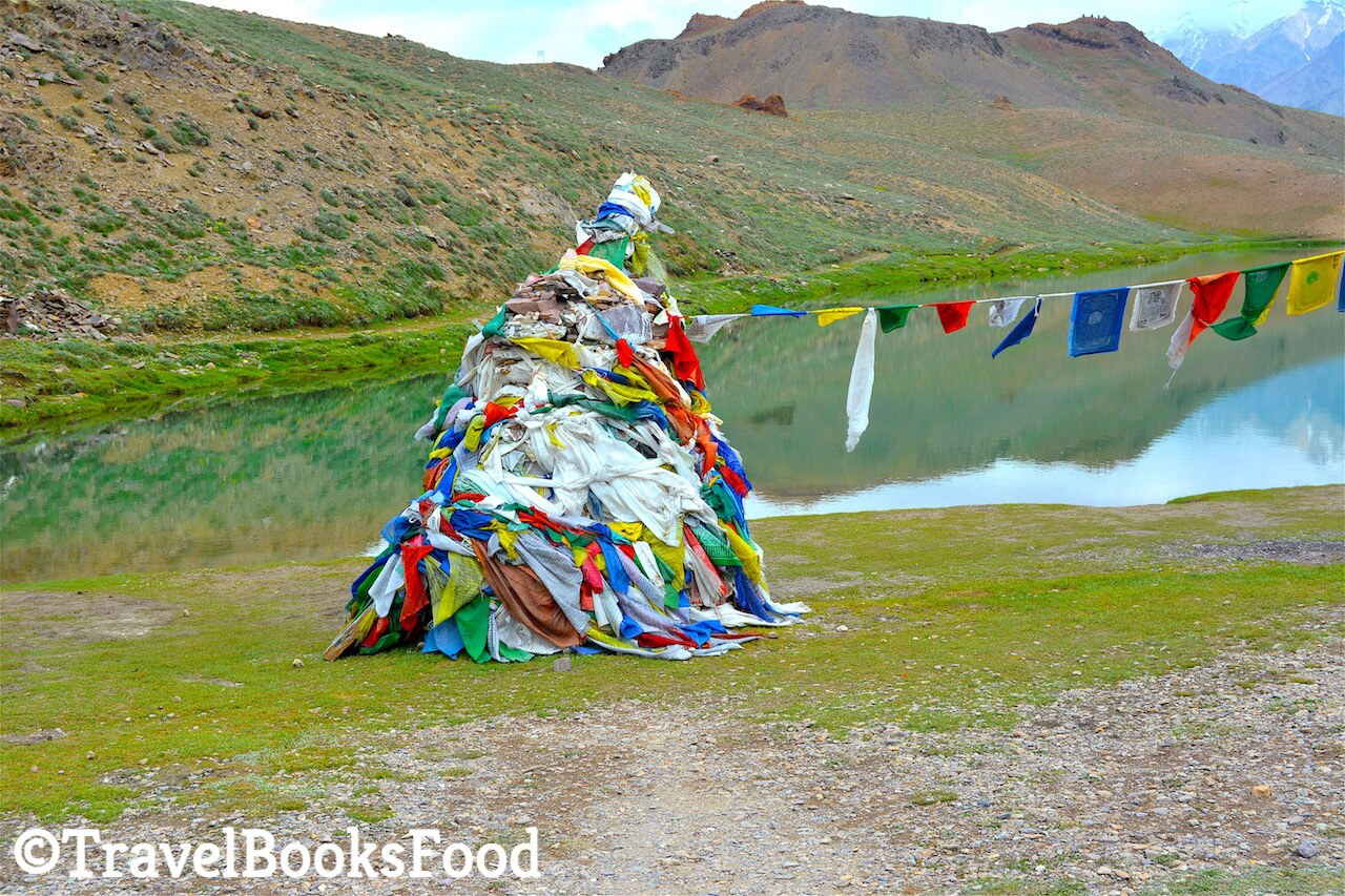 Buddhist prayer flags sitting at the edge of the blue Chandrataal lake