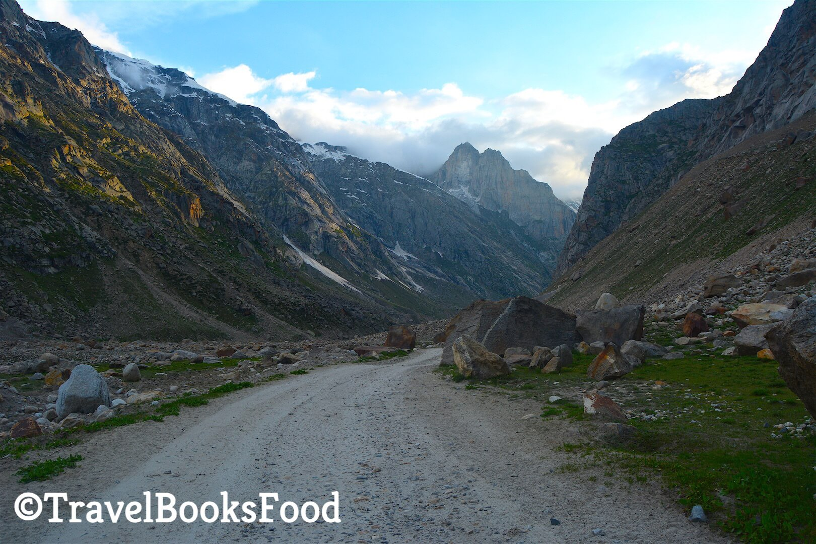 A gravel road in the middle of many mountains and some huge rocks