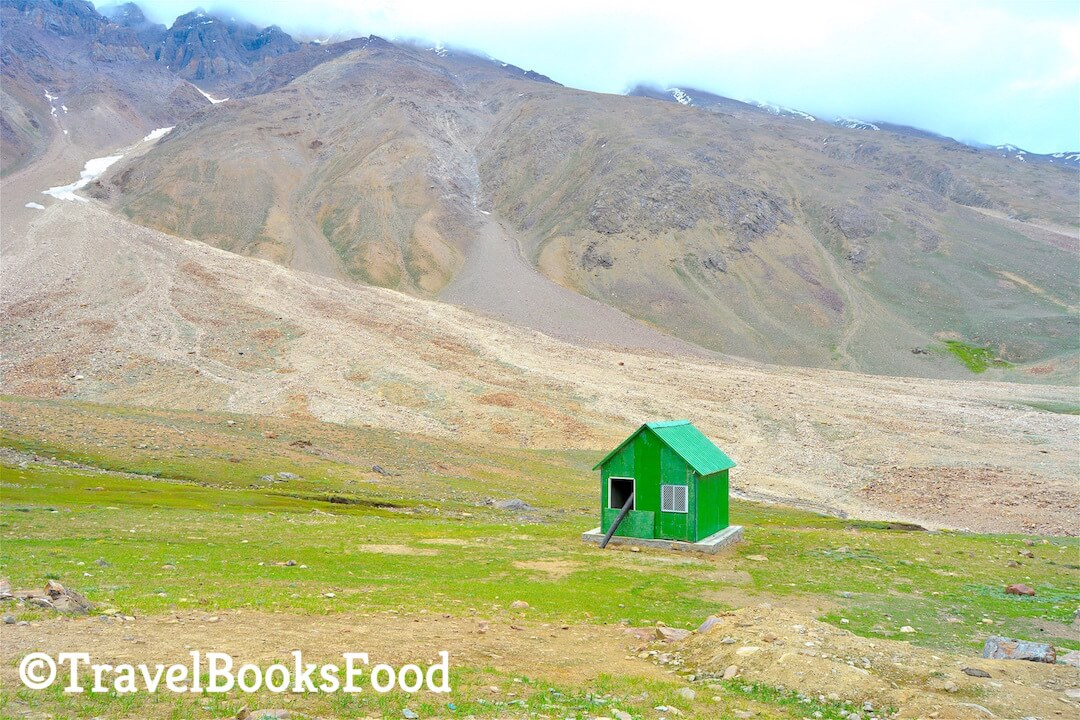 A green shed surrounded by mountains in a vast green field