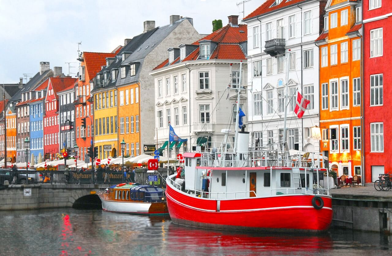A row of colourful houses with a harbour and couple of boats in front of them in Copenhagen, Denmark