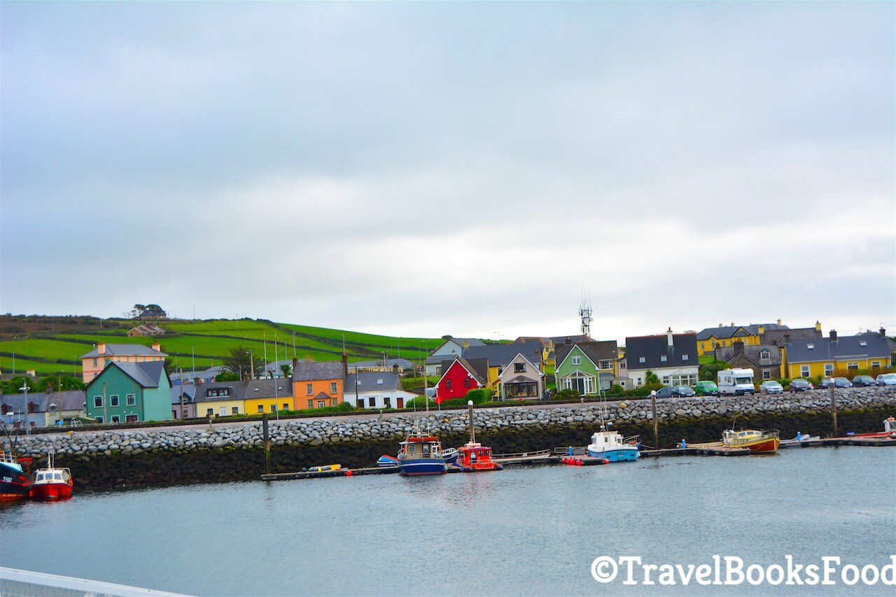 This is a photo of the town of Dingle in Ireland of colourful houses taken from a boat. You can see green fields in the distance