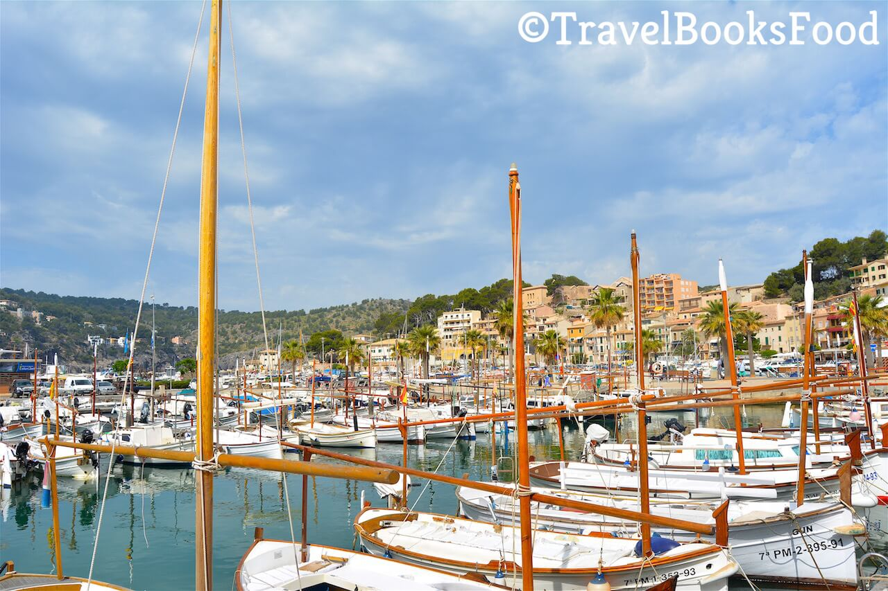 A photo of the marina of Port de soller in Mallorca, Spain. You can see lots of white boats and few cream coloured houses in the distance