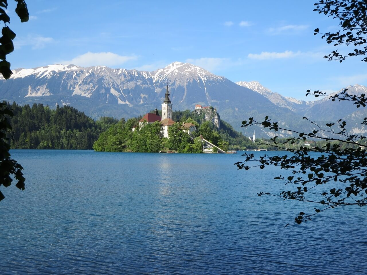 A photo of Lake Bled with a town in the distance and few mountains surrounding it