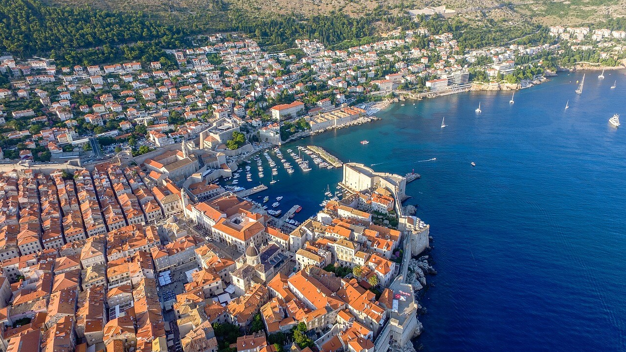 A photo of the city of Dubrovnik from above. In this photo, you can see the marina and the brown tiled buildings along the harbour