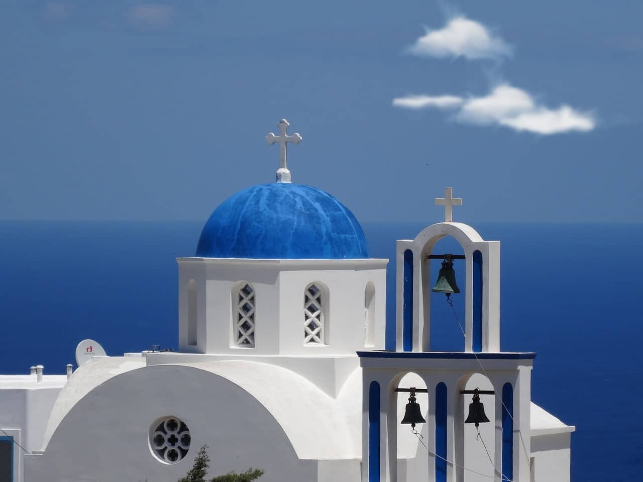 A photo of a white church with a blue dome with the sea in the background in Santorini, Greece