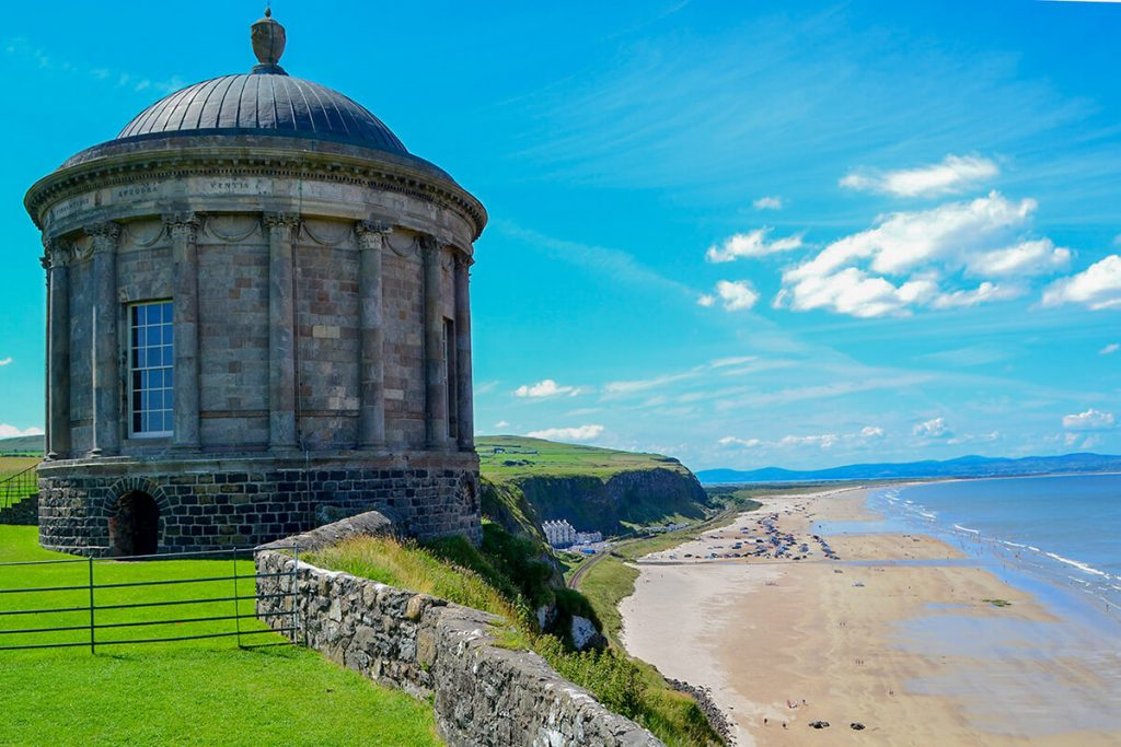 A photo of a building with a round dome on a cliff besides a sandy beach in Northern Ireland