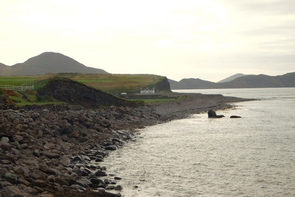 A picture of a shore with black rocks and hills in the distance