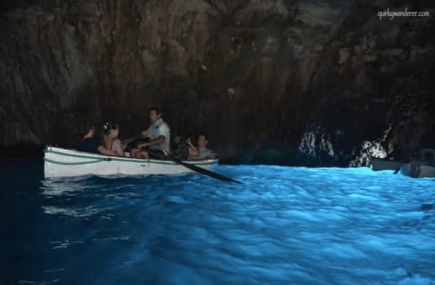 A picture of a boat in a cave with blue water