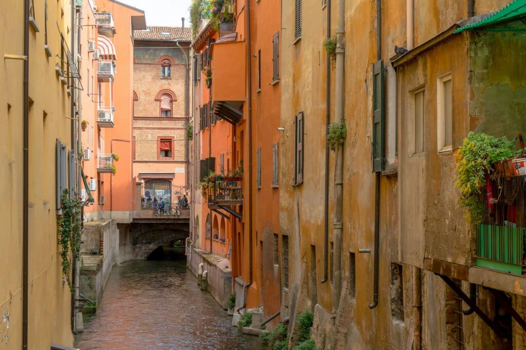 A photo of a street with colourful buildings in Bologna, Italy