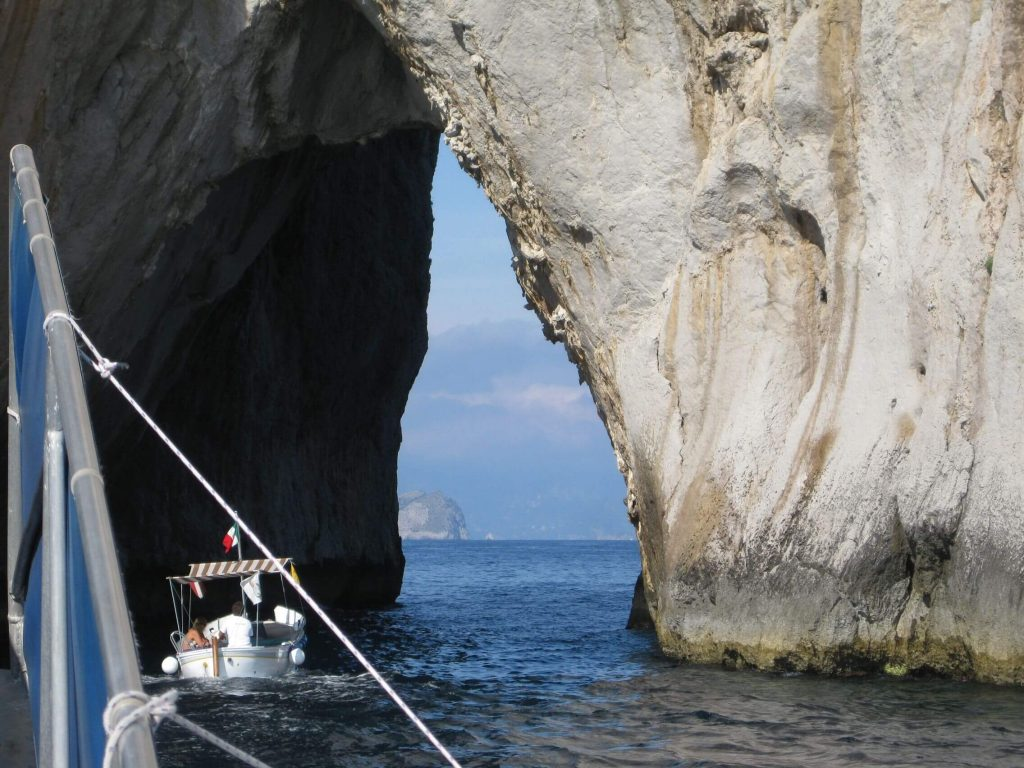 A photo of a boat doing through two cliffs or a cave