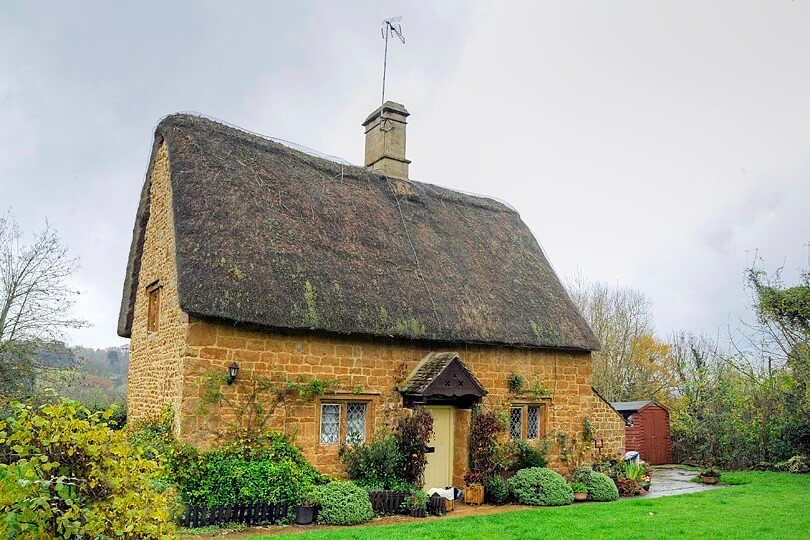 A photo of a thatched cottage in Cotswold with a pretty garden