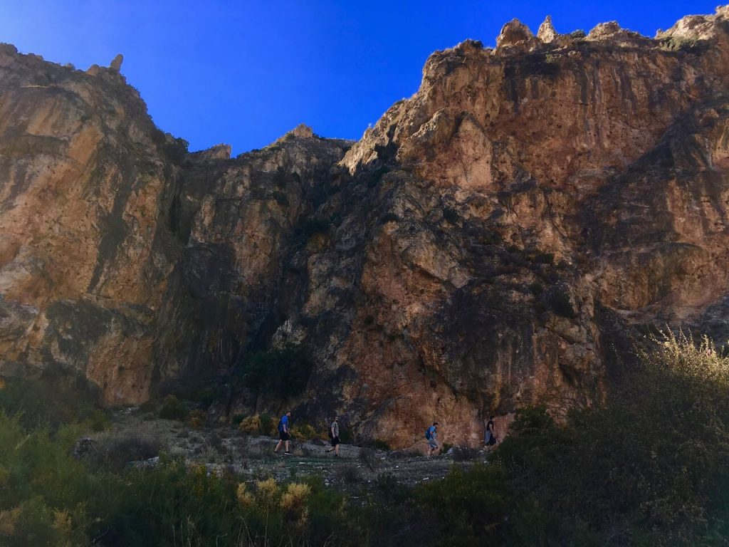 A photo of a brown mountain with some people hiking