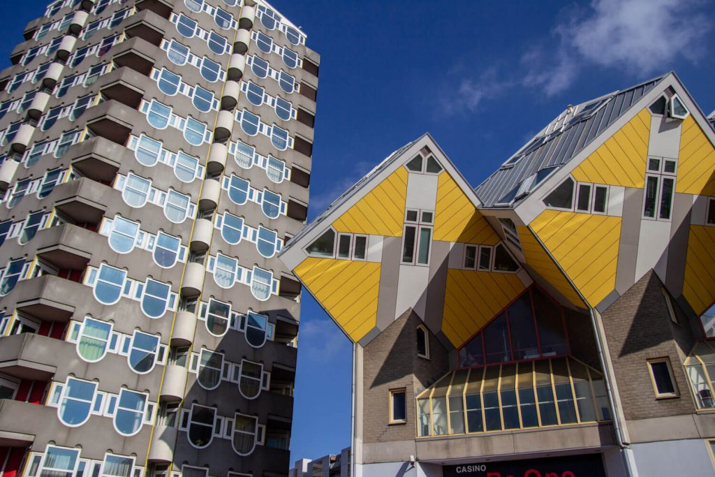 A picture of the yellow cube houses in Rotterdam next to a cylindrical building