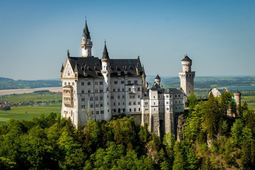 Picture of the Neuschwanstein castle from a distance on top of a hilltop