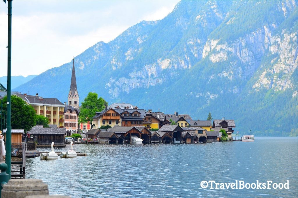In this photo, you see a picture of a quaint village surrounded by water and hills. Travel Bloggers Pick Their Choice Of Best Europe Day Trips For Your Eurotrip itinerary