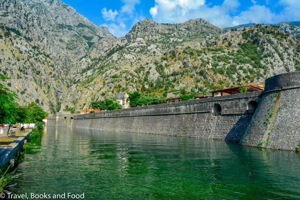 The fortified walls ok Kotor against the mountains and some really green water