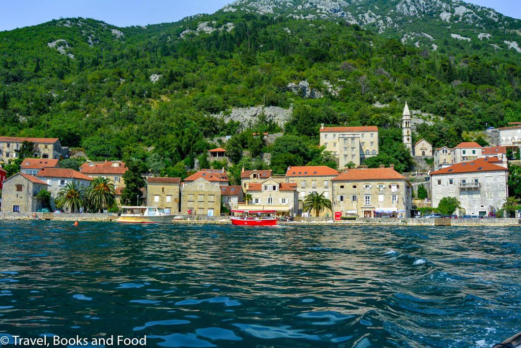 In this photo, you see a coastal town set up against some green mountains with orange roofs and blue water in Perast, Montenegro