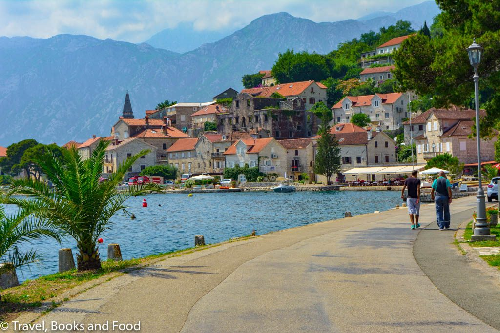 Another photo of the Montenegro coast with a church and some orange tiled buildings set up against the black mountains of Montenegro and clear blue water
