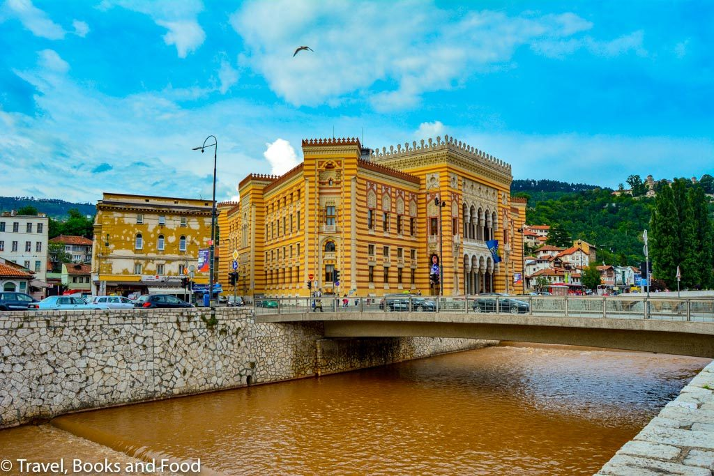 Sarajevo City Hall which is an orange/dark pink building surrounded by a dirty river. One of your stops in your Sarajevo itinerary