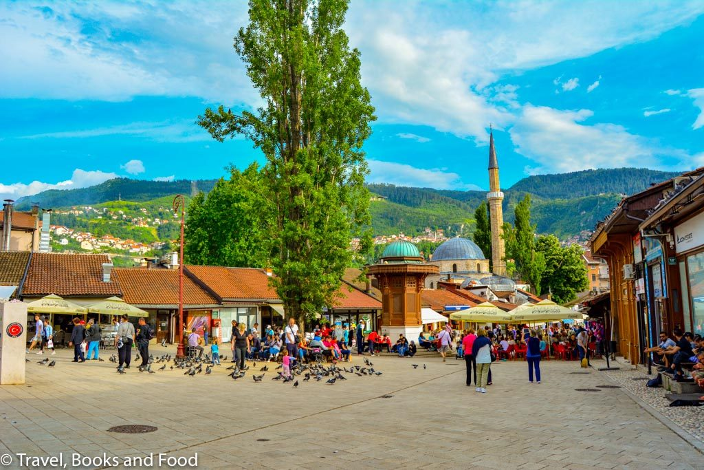 Old Town Square in Sarajevo with lots of people, a mosque, a fountain and pigeons
