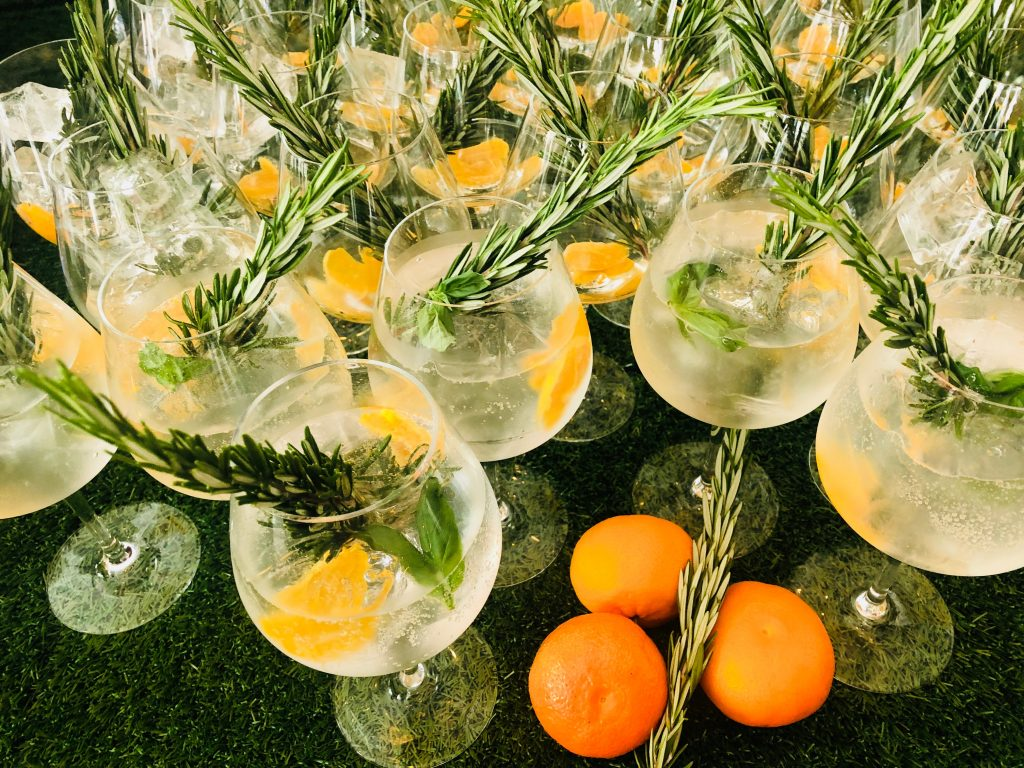 Lots of glasses with Gin and Tonic served with orange slices set on a table on a green background