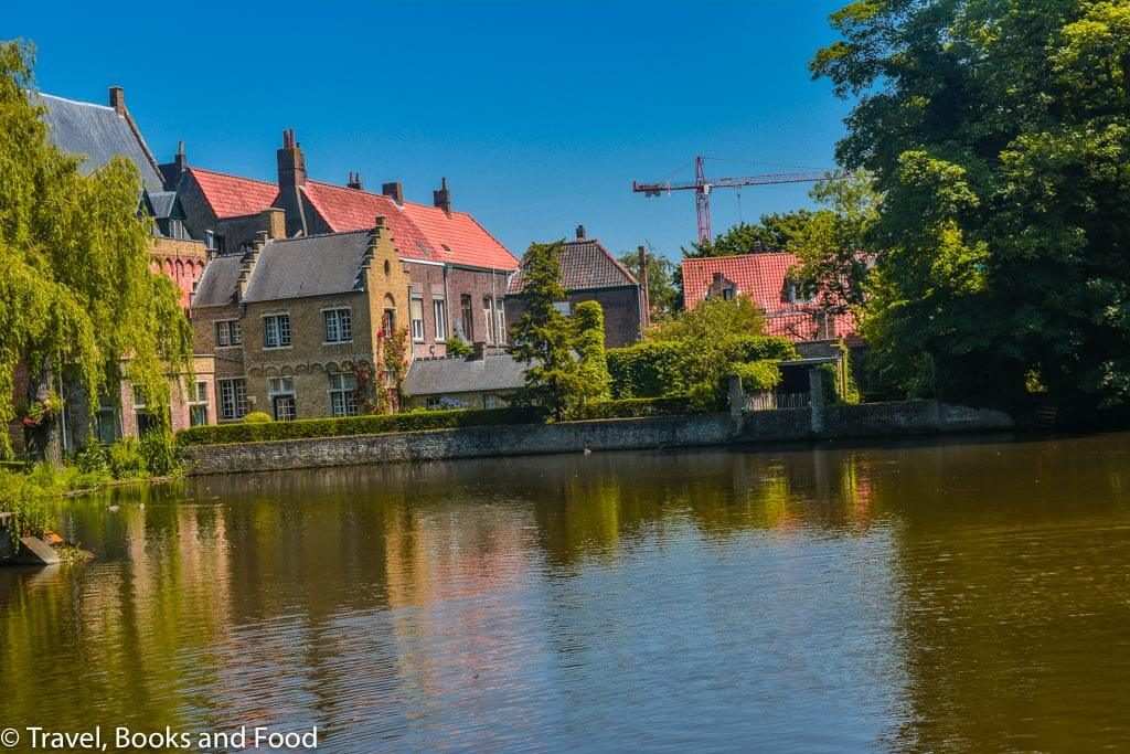 The pretty UNESCO heritage site of Bruges with canals, trees and buildings with orange tiles